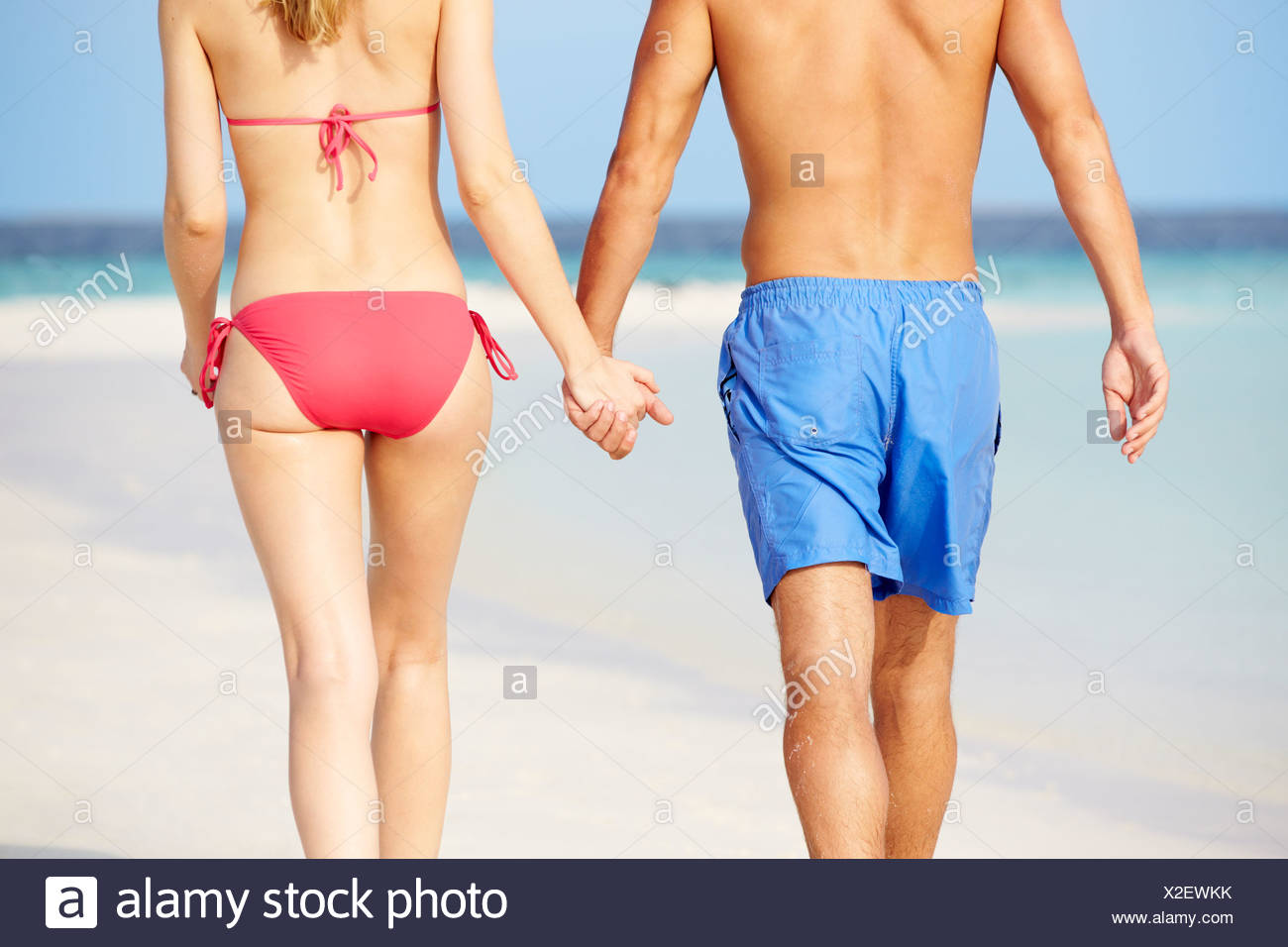 Close Up Of Romantic Couple Walking On Tropical Beach - Stock Image