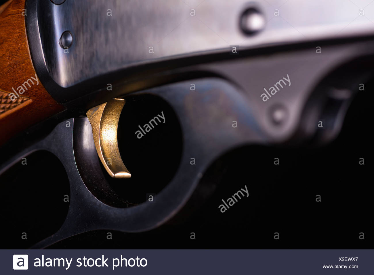 Trigger of gun against black background, close up - Stock Image