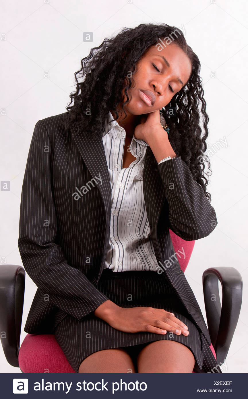Businesswoman resting on chair with eyes closed and head in hand - Stock Image
