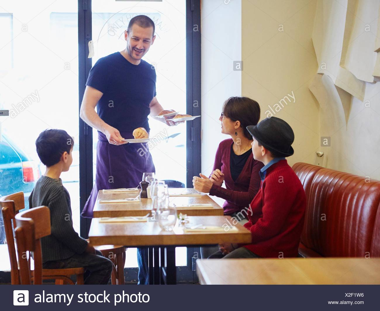 Waiter serving lunch in restaurant to woman and sons - Stock Image