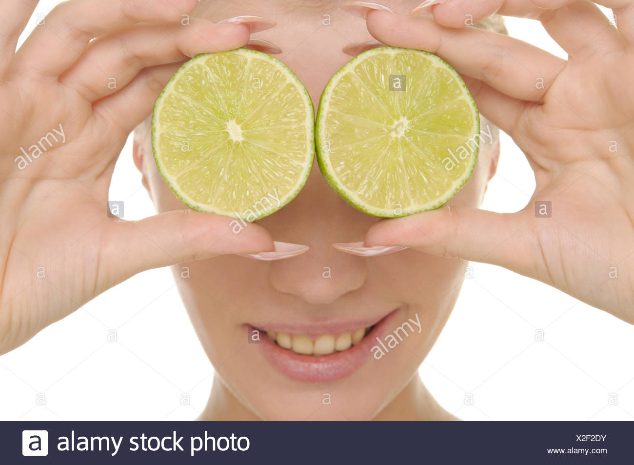 Young woman holds halves of lime before eyes Stock Photo