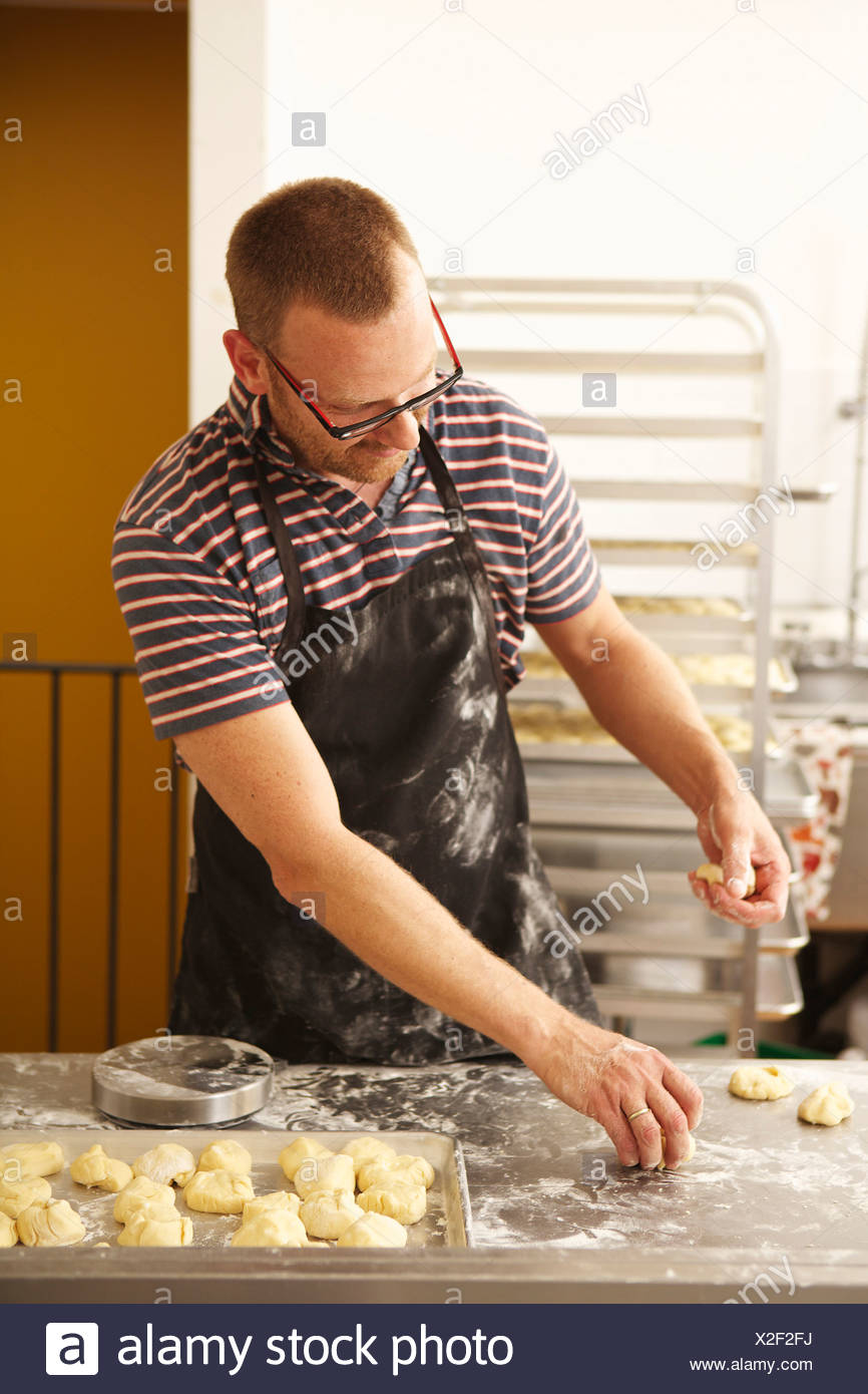 Male baker shaping dough in bakery - Stock Image