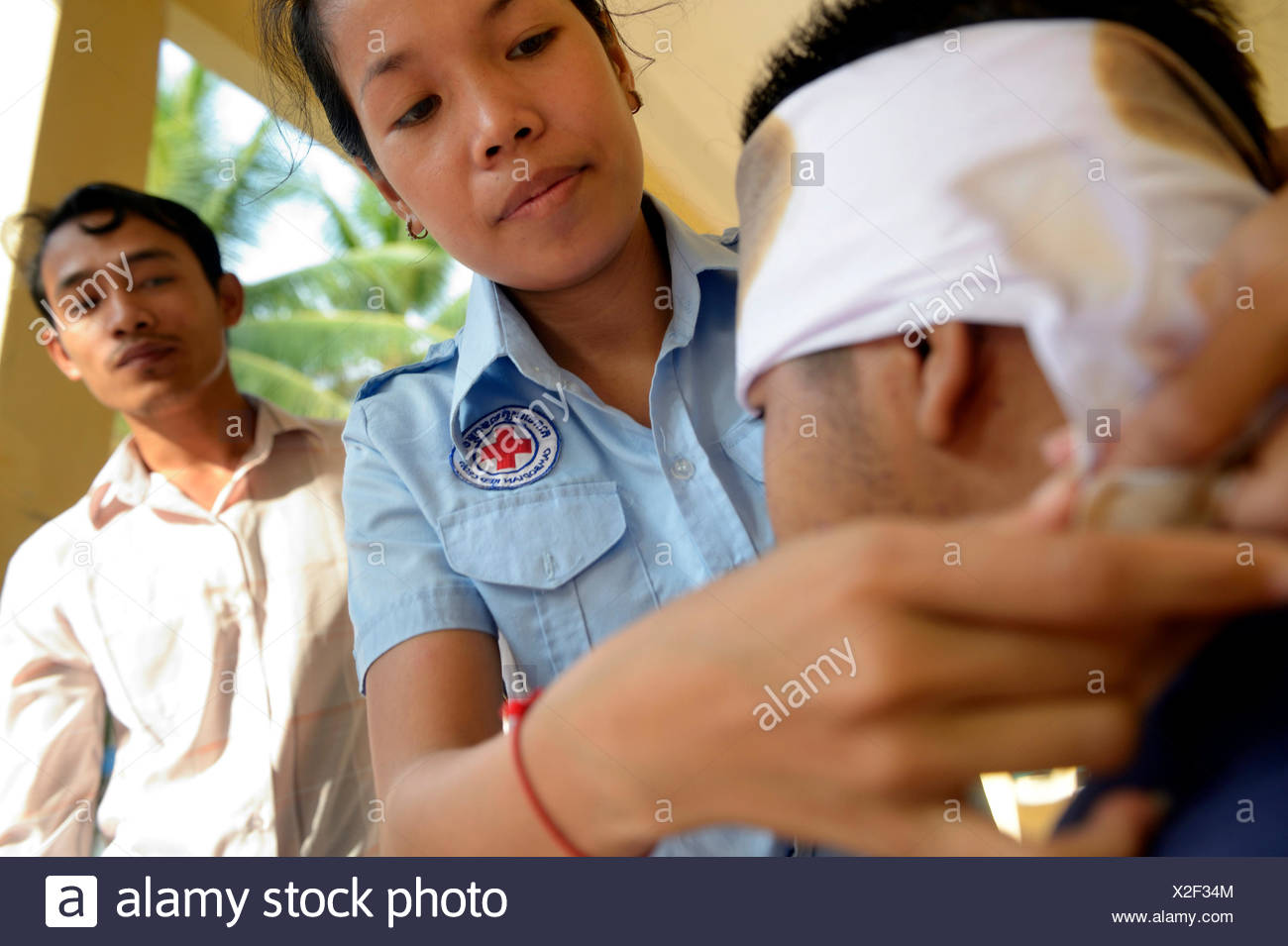 Young woman applying a head bandage, training of young people from the community to become first aid workers by the Red Cross - Stock Image