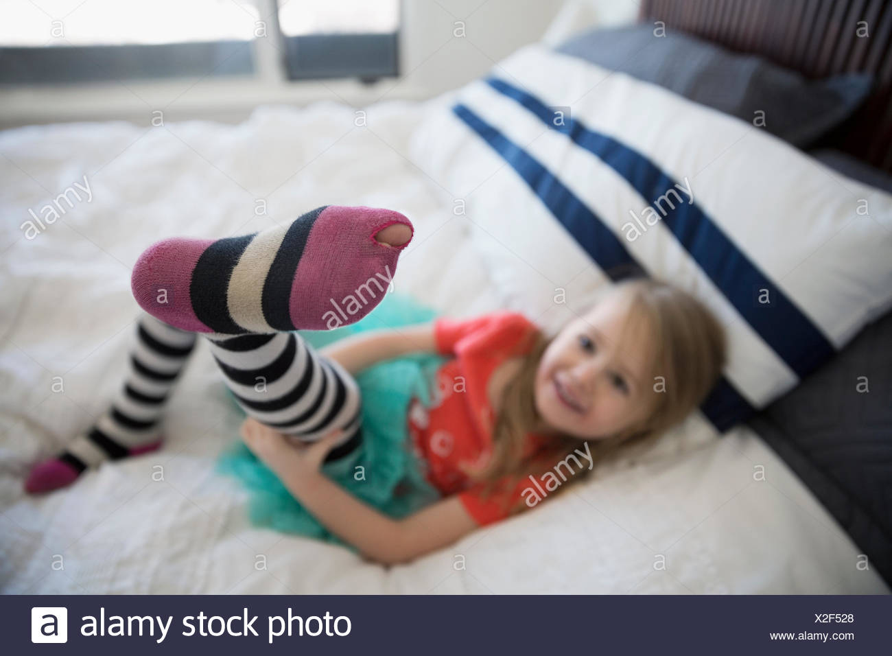 Cute girl showing toe poking from hole leggings - Stock Image
