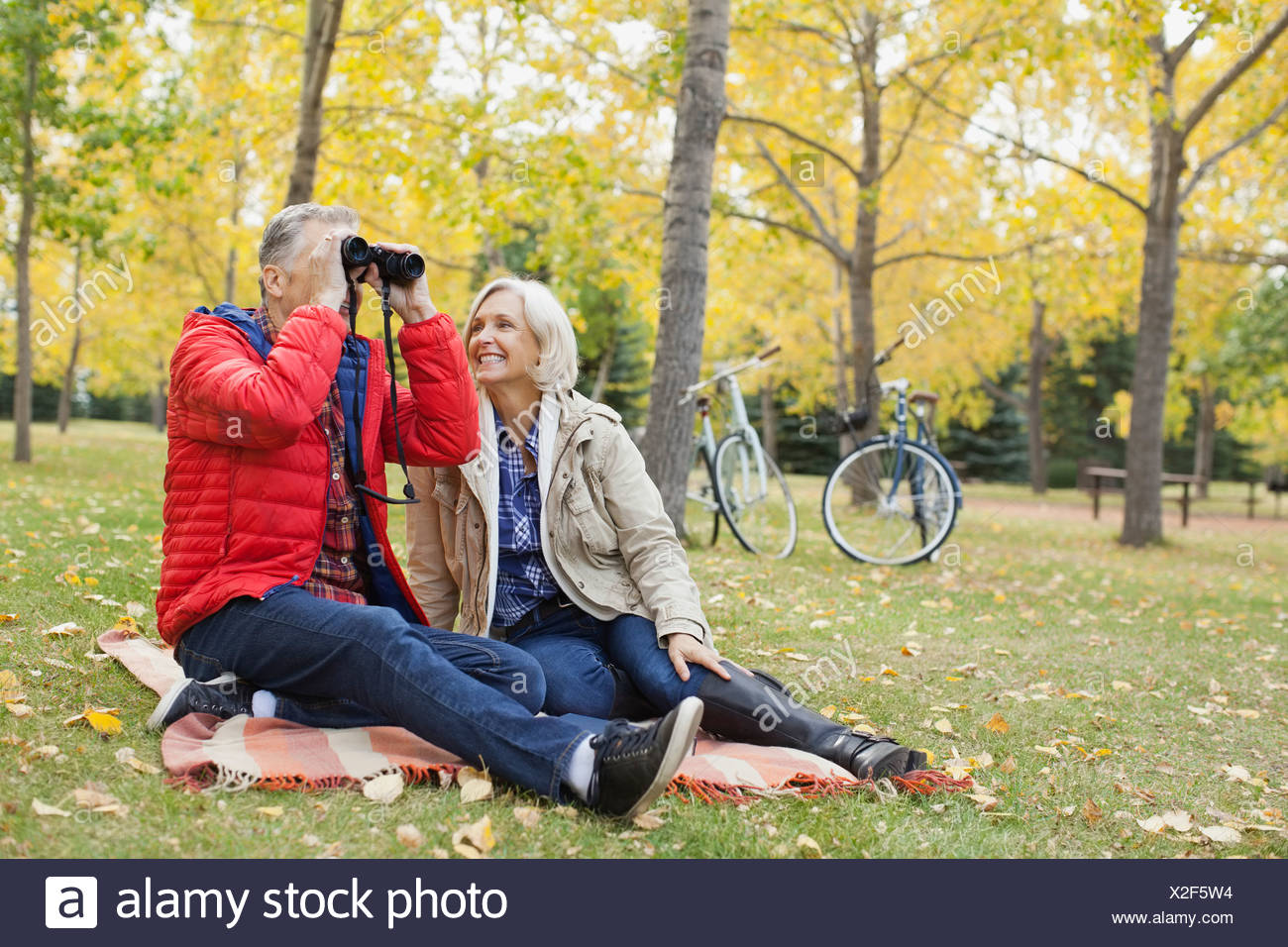 Full length of smiling woman with man looking through binoculars at park - Stock Image
