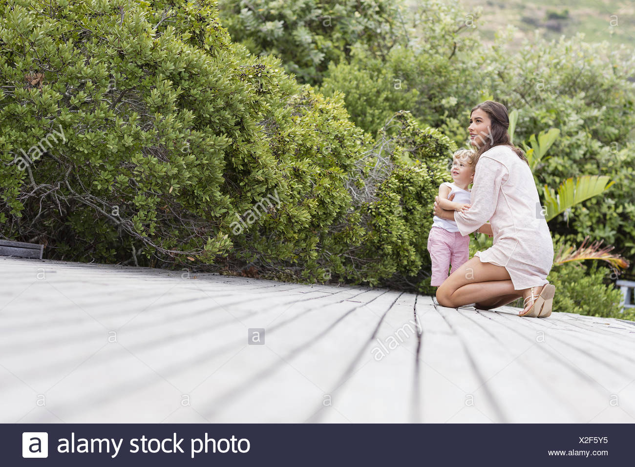 Happy mother and son on deck in garden - Stock Image
