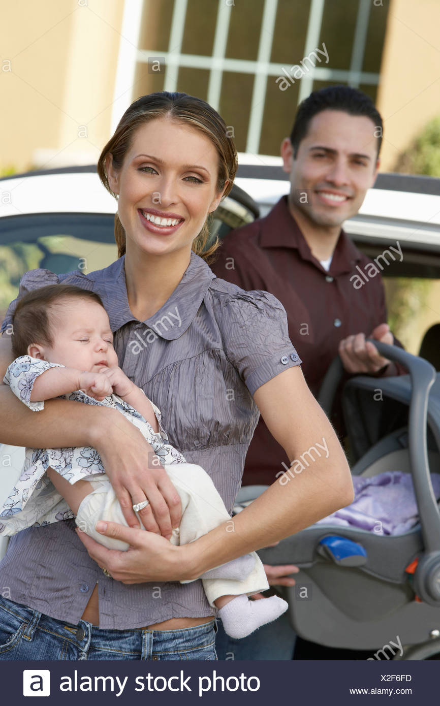 Portrait of woman with baby (1-6 months) by car, man in background - Stock Image