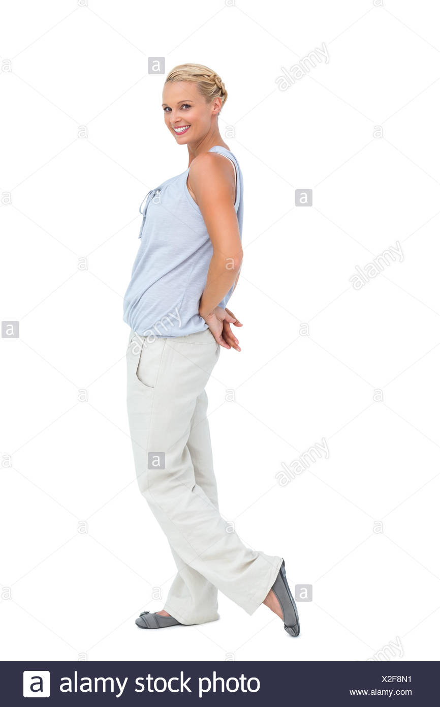 Woman looking at camera with hands behind her back - Stock Image