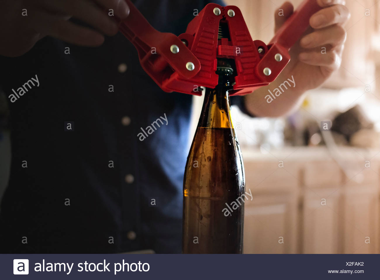 Close up of man using crown corker for closing bottle top of home brew beer - Stock Image