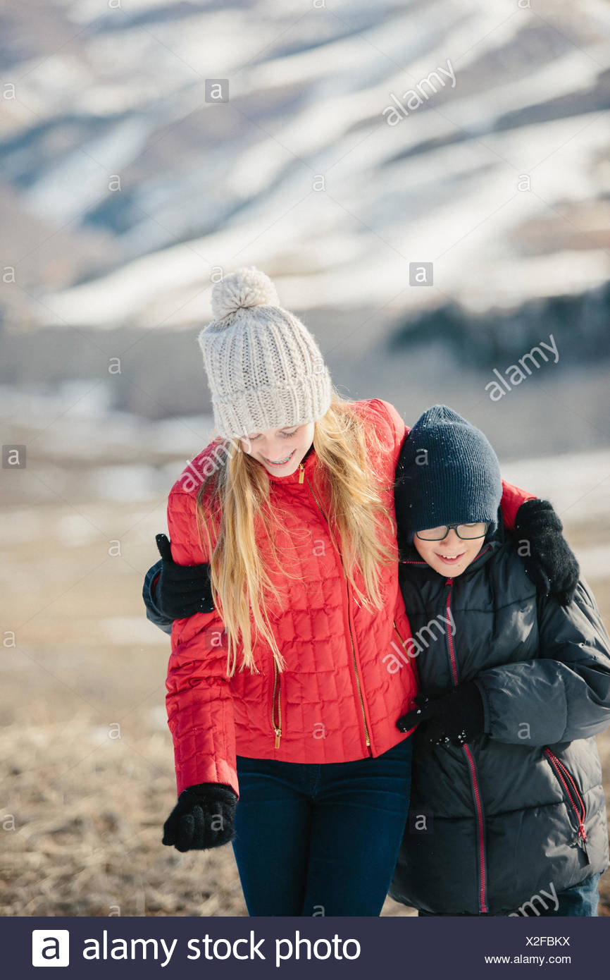 A brother and sister hugging and laughing together outdoors. - Stock Image