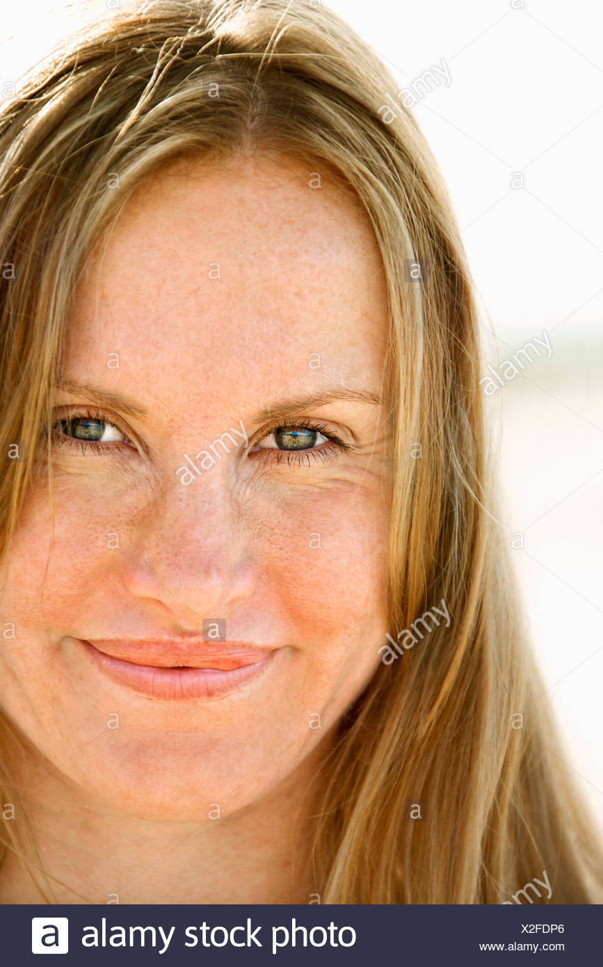 Close up portrait of attractive redheaded woman looking at viewer - Stock Image
