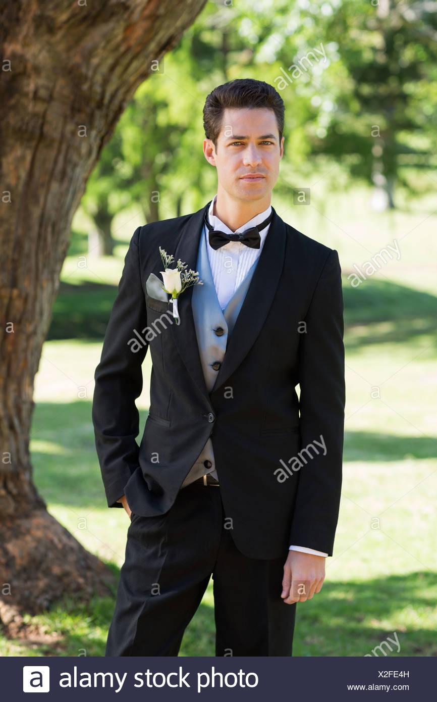Confident bridegroom in tuxedo at garden - Stock Image