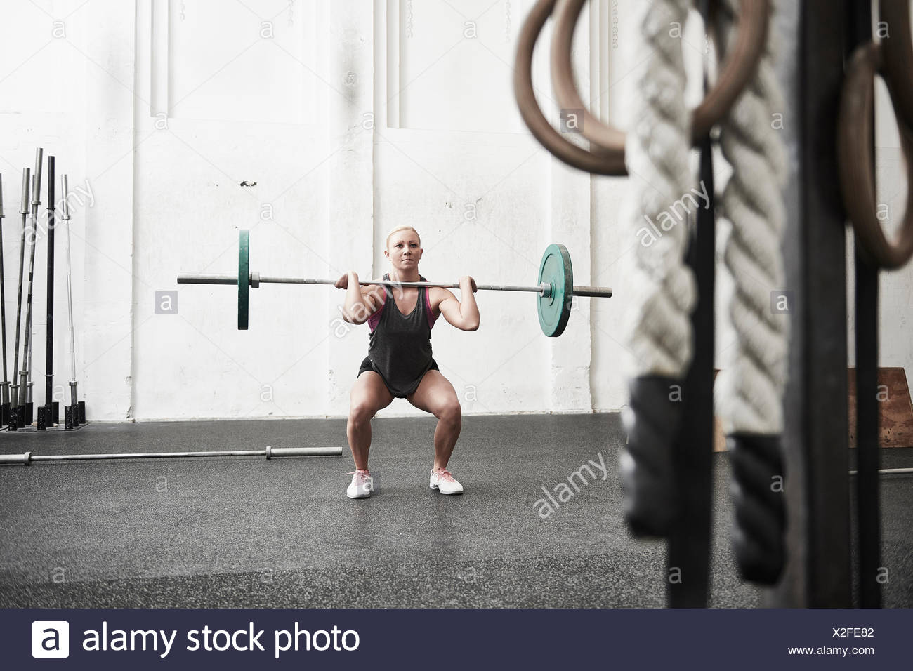 Woman lifting barbell in cross training gym - Stock Image