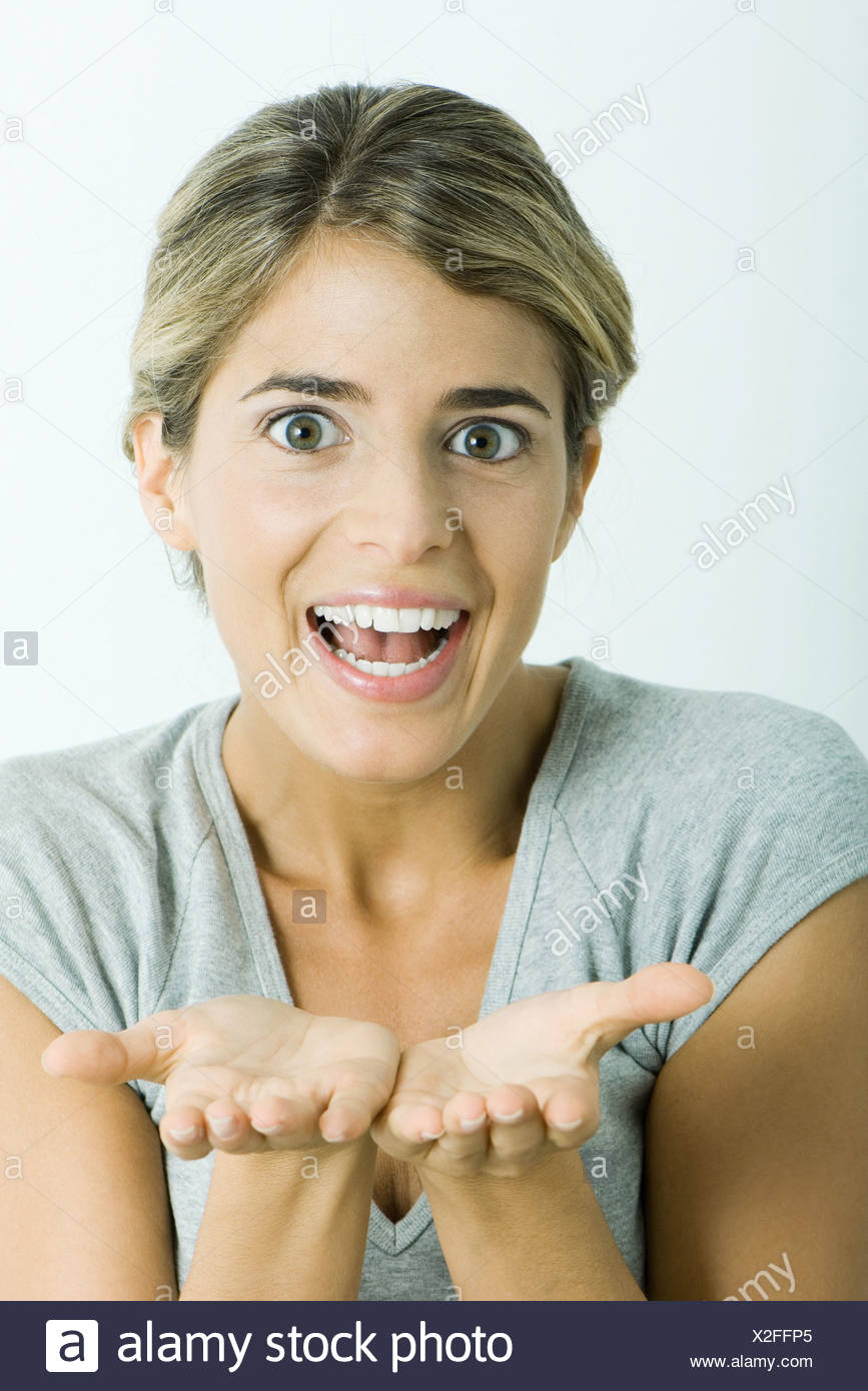 Woman, smiling at camera, holding out palms, portrait - Stock Image