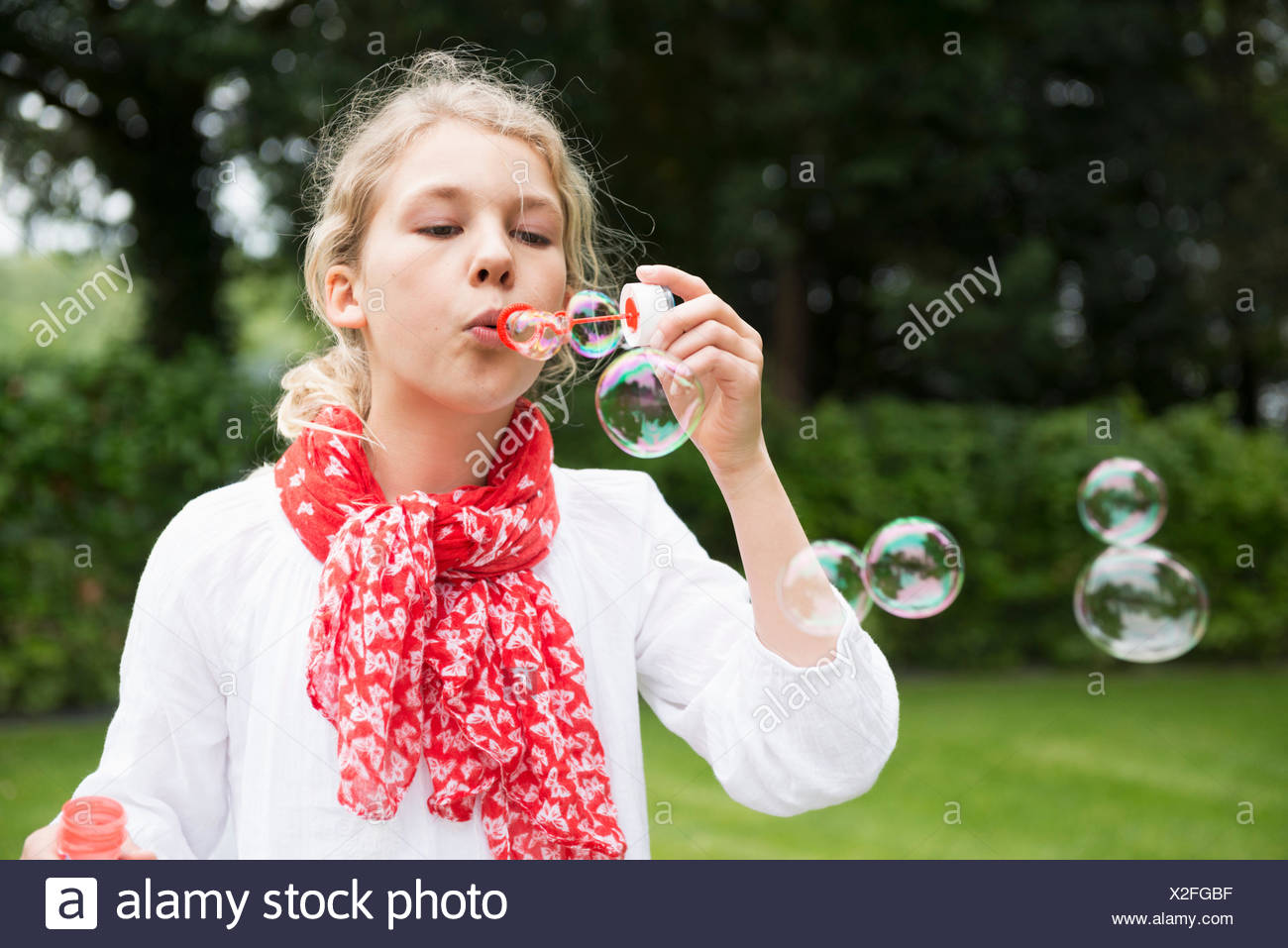 Girl blowing bubbles - Stock Image