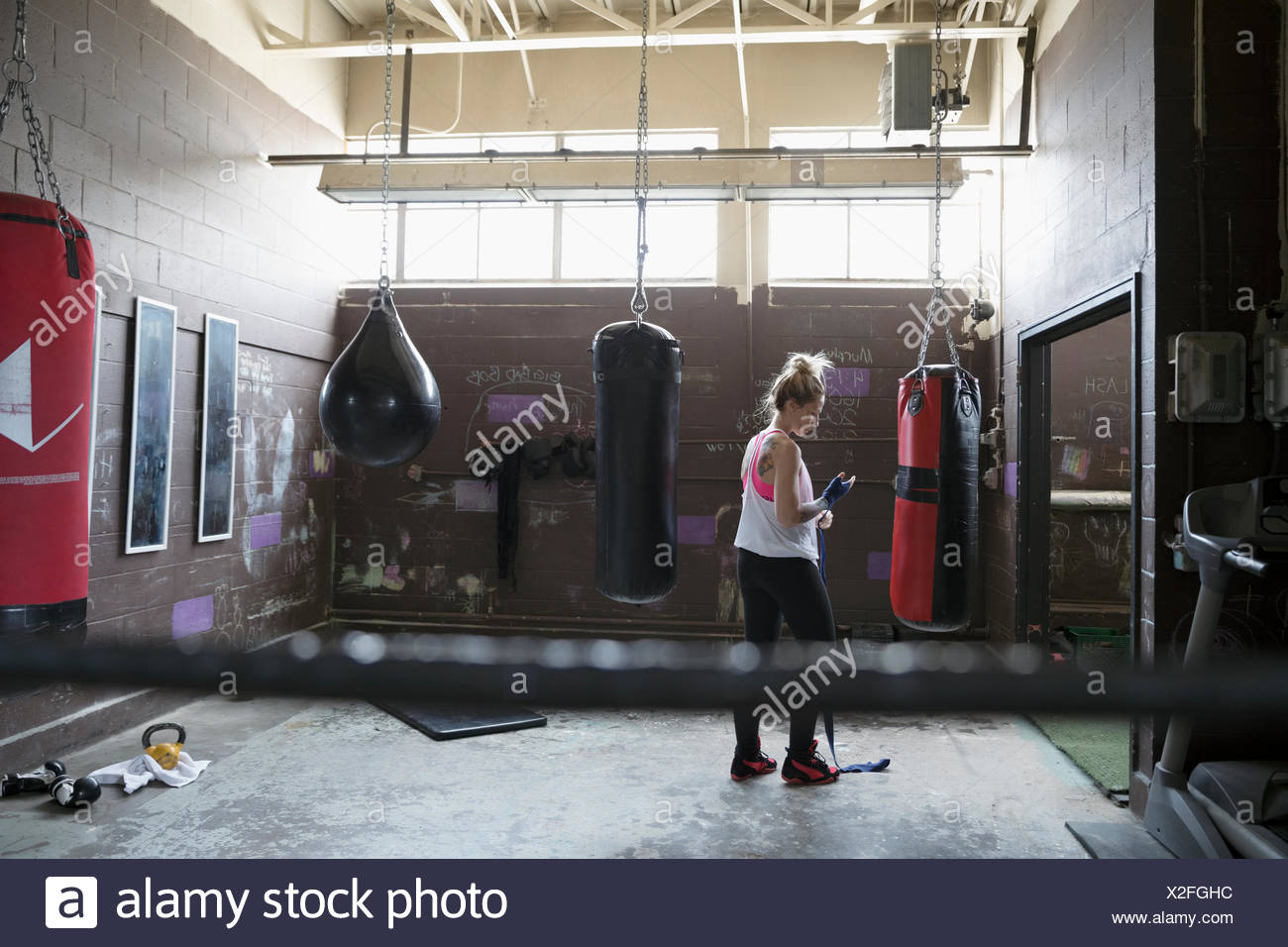 Female boxer wrapping wrist at punching bag in gritty gym - Stock Image