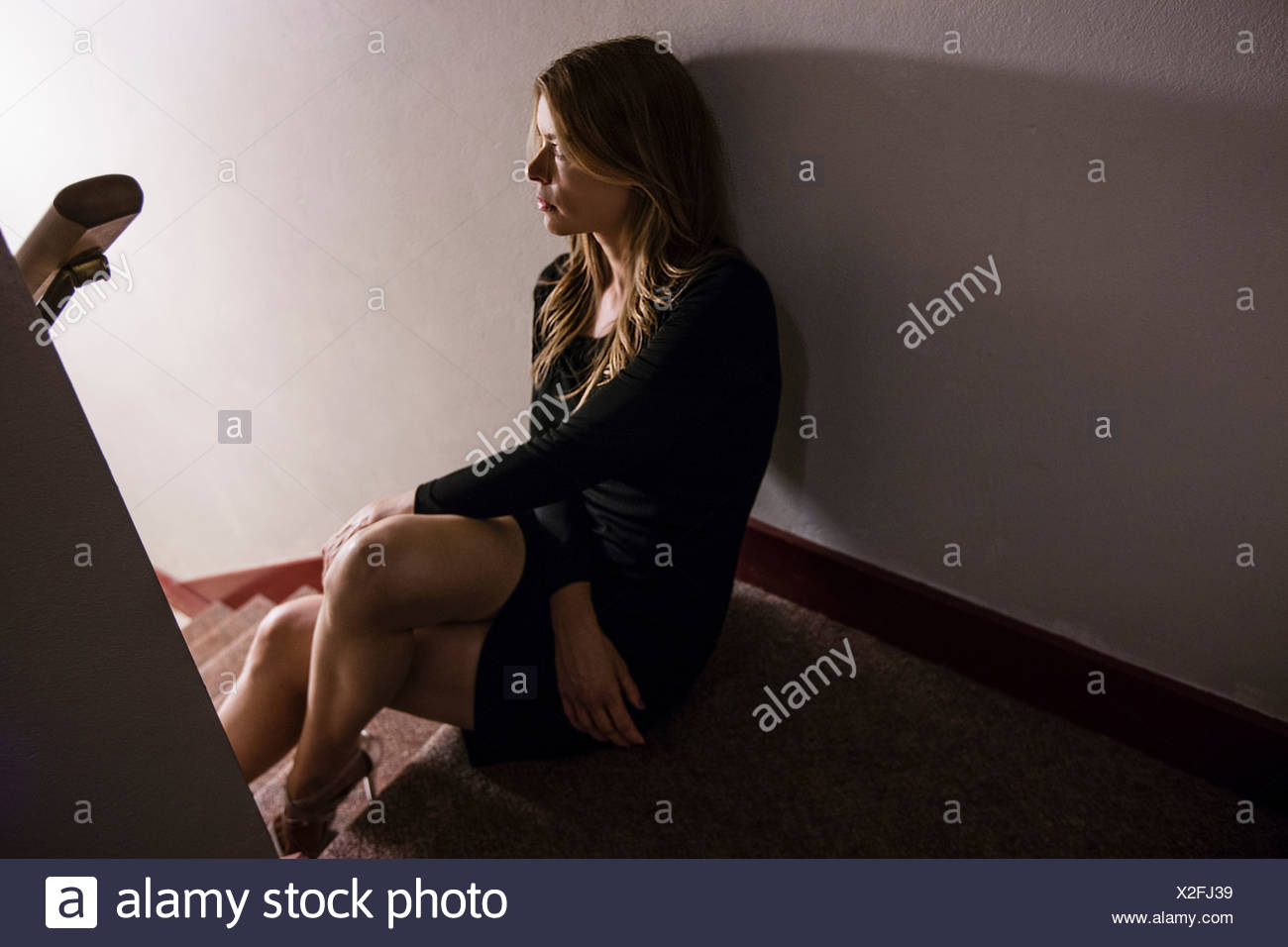 Mature woman sitting on staircase, looking away - Stock Image