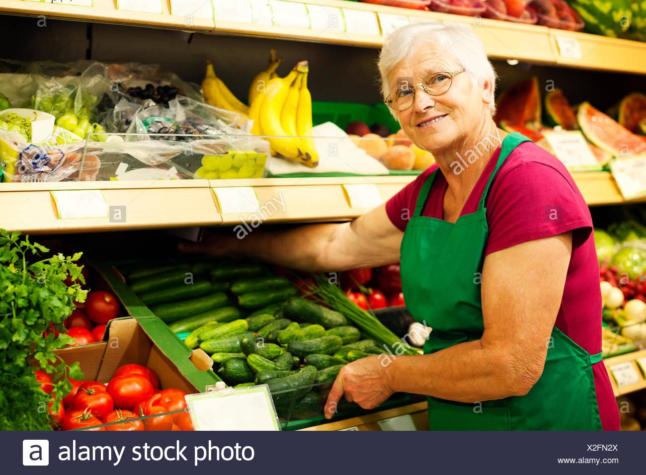 Senior woman arranging vegetables on shelf Debica, Poland - Stock Image