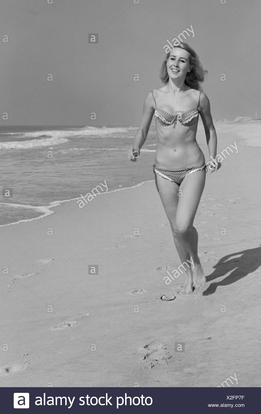 Young woman in bikini walking on beach - Stock Image