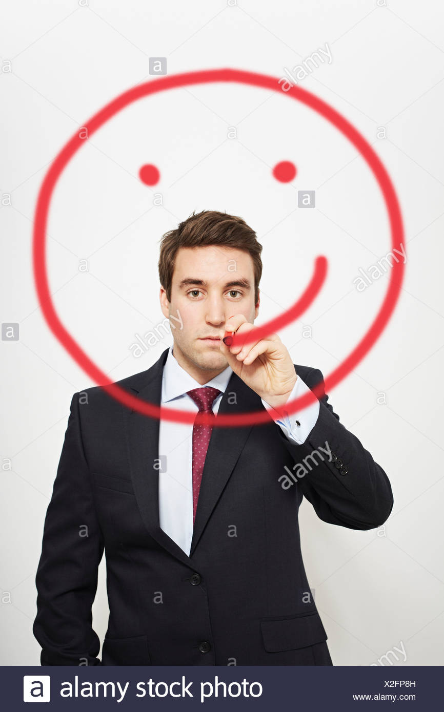 Businessman drawing smiley face in air - Stock Image