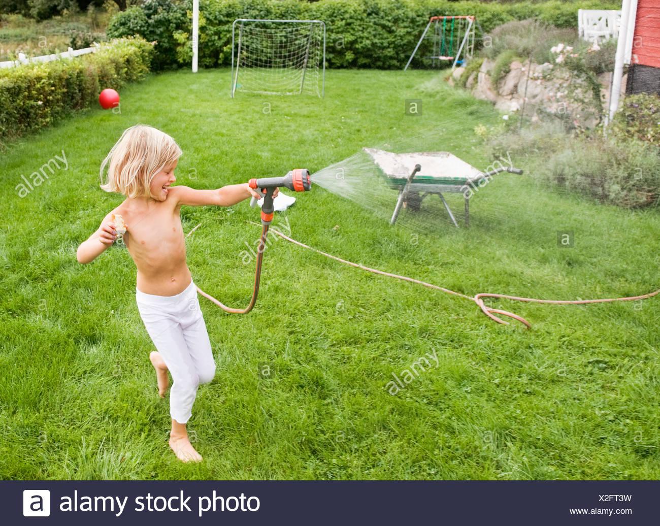 Girl holding water hose - Stock Image