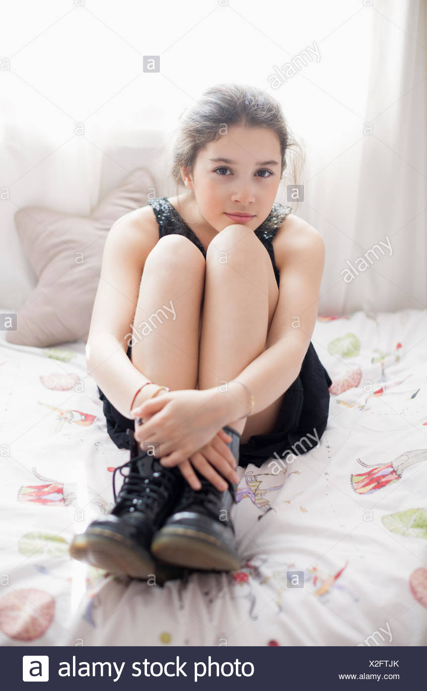 Girl sitting on bed - Stock Image