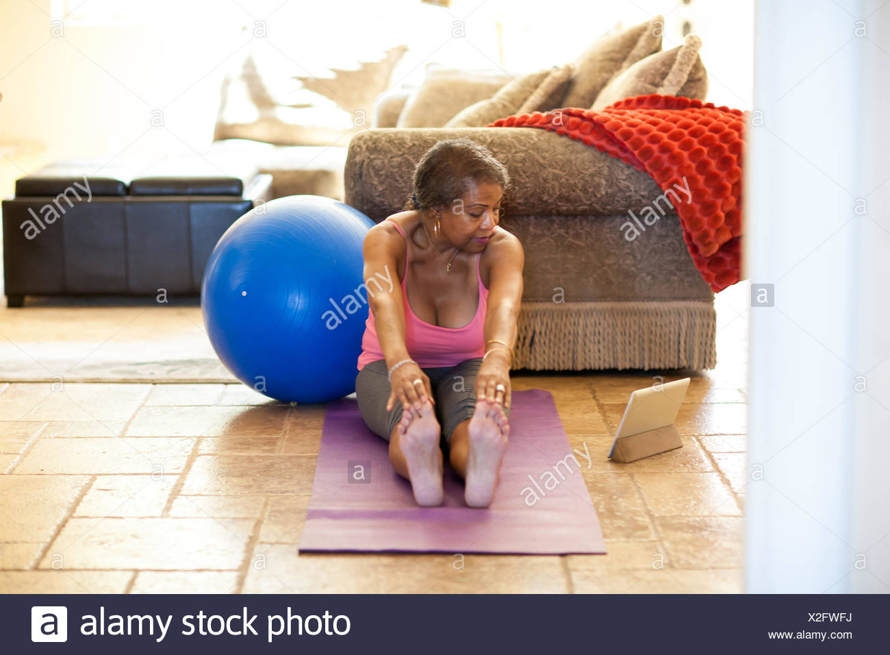 Woman on yoga mat using digital tablet, stretching - Stock Image