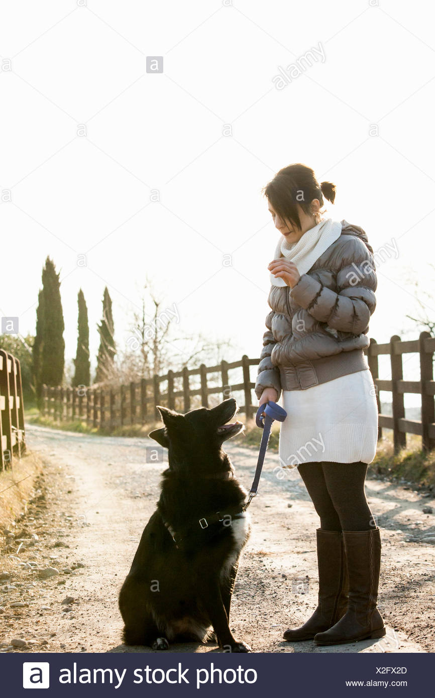 Mid adult woman obedience training her dog on rural road - Stock Image