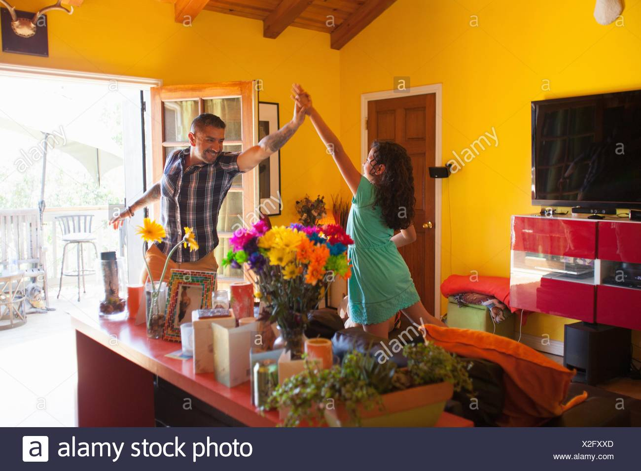 Girl giving father high five in living room - Stock Image