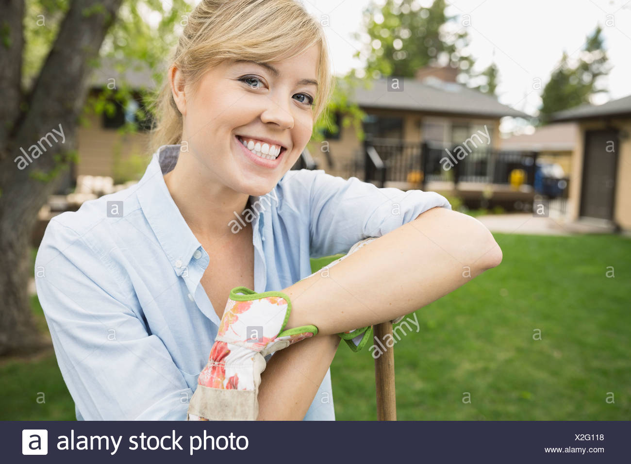 Portrait of smiling woman wearing gardening gloves - Stock Image
