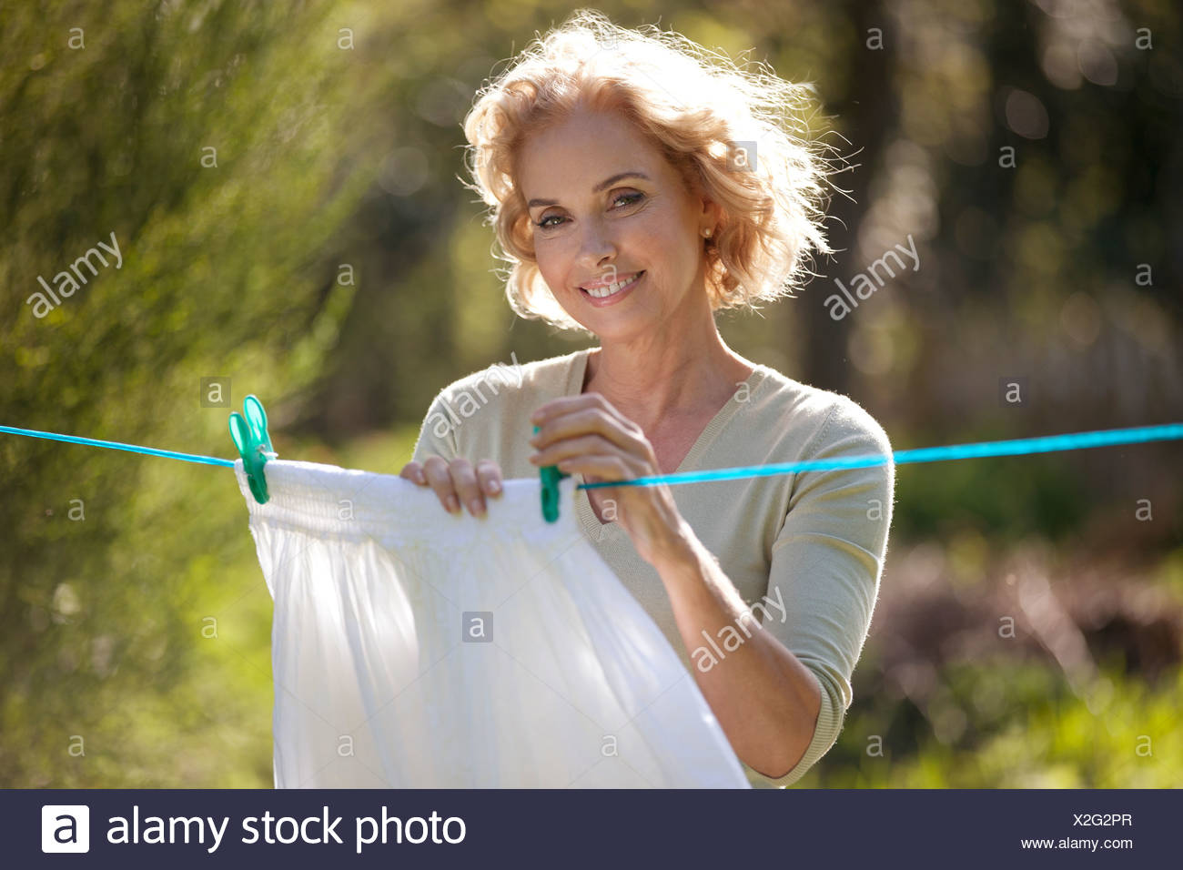 A mature woman pegging out washing on a washing line - Stock Image