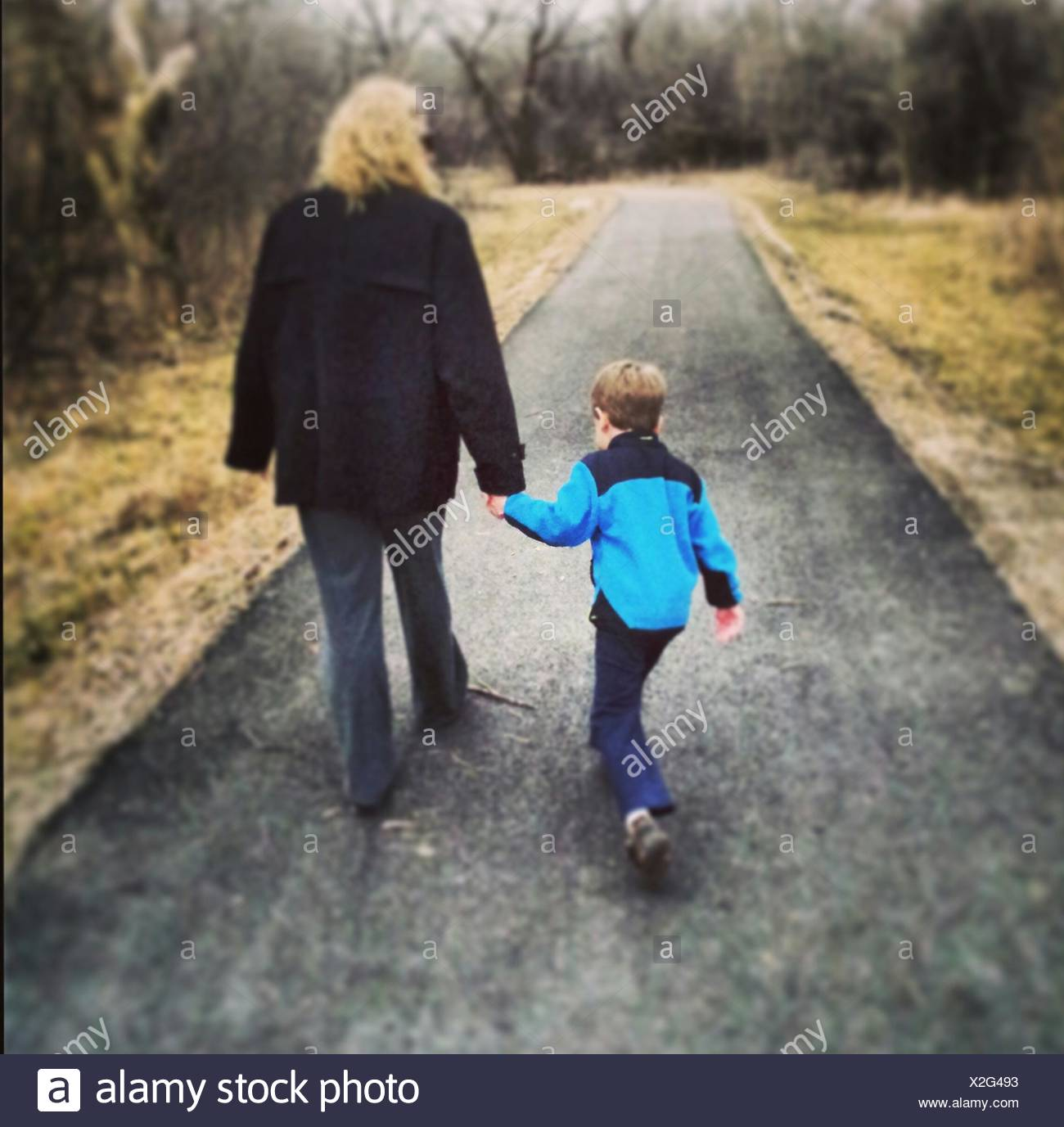 Rear View Of Woman And Boy Walking On Country Road - Stock Image