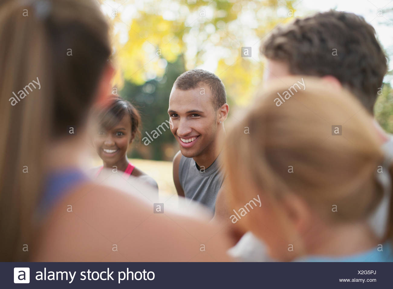 Outdoor fitness class standing and talking together. - Stock Image