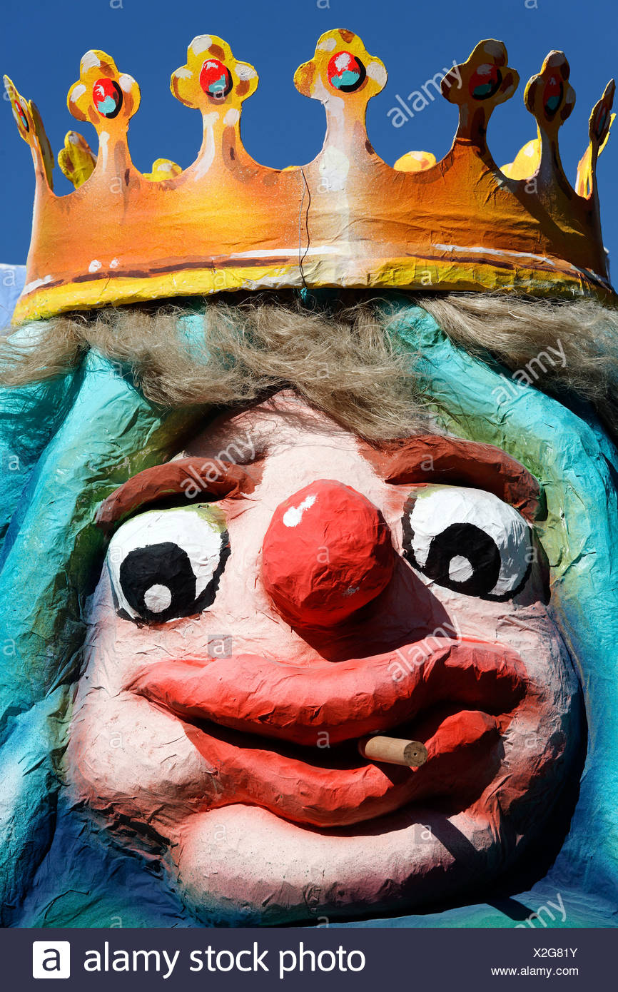 King wearing a crown with a comical facial expressions, smokes cigarillos, paper-mache figure, parade float at the - Stock Image