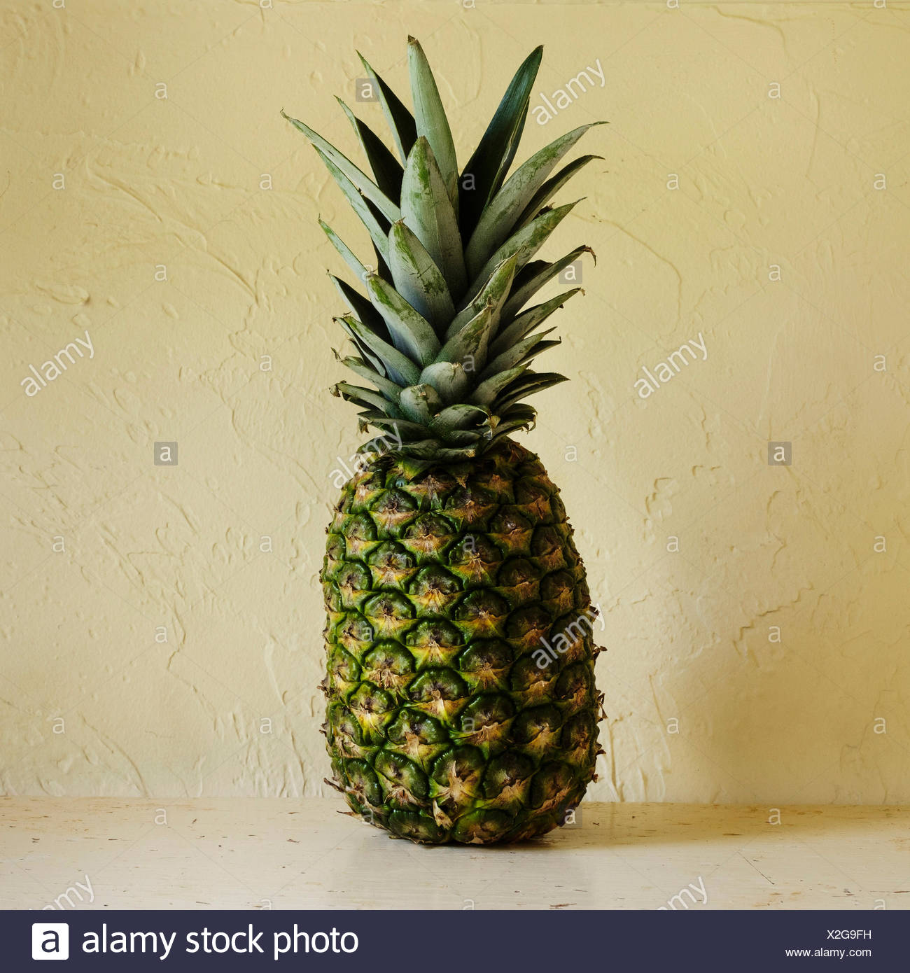 Fresh pineapple against textured wall - Stock Image