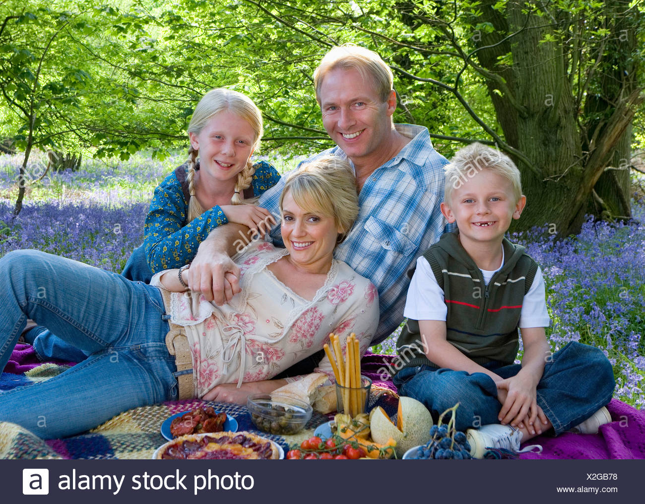 Family picnicking in field of bluebell flowers - Stock Image