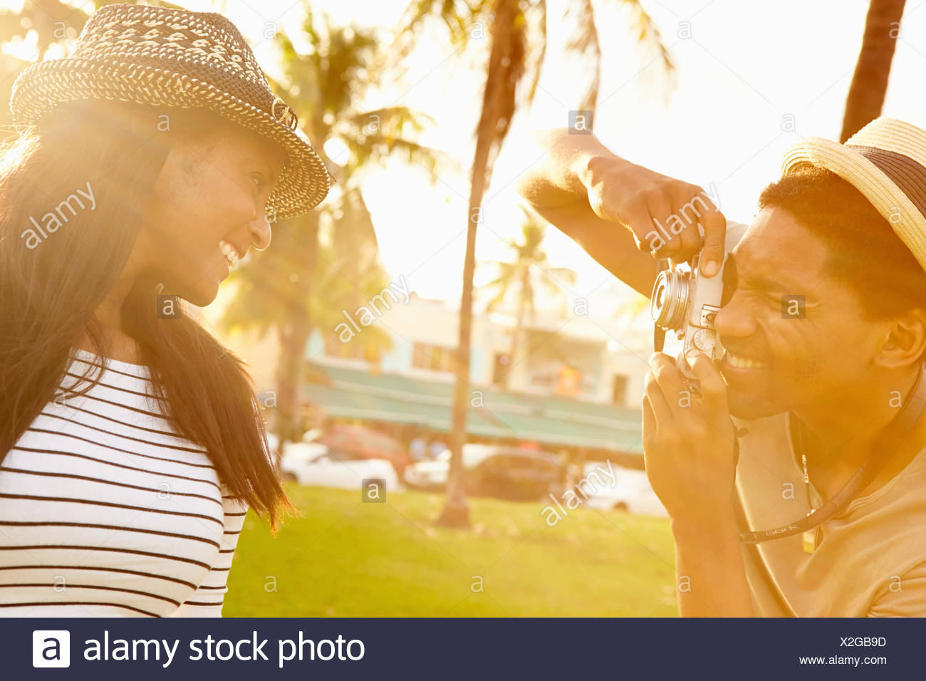 Man Taking Photograph Of Woman In Park - Stock Image