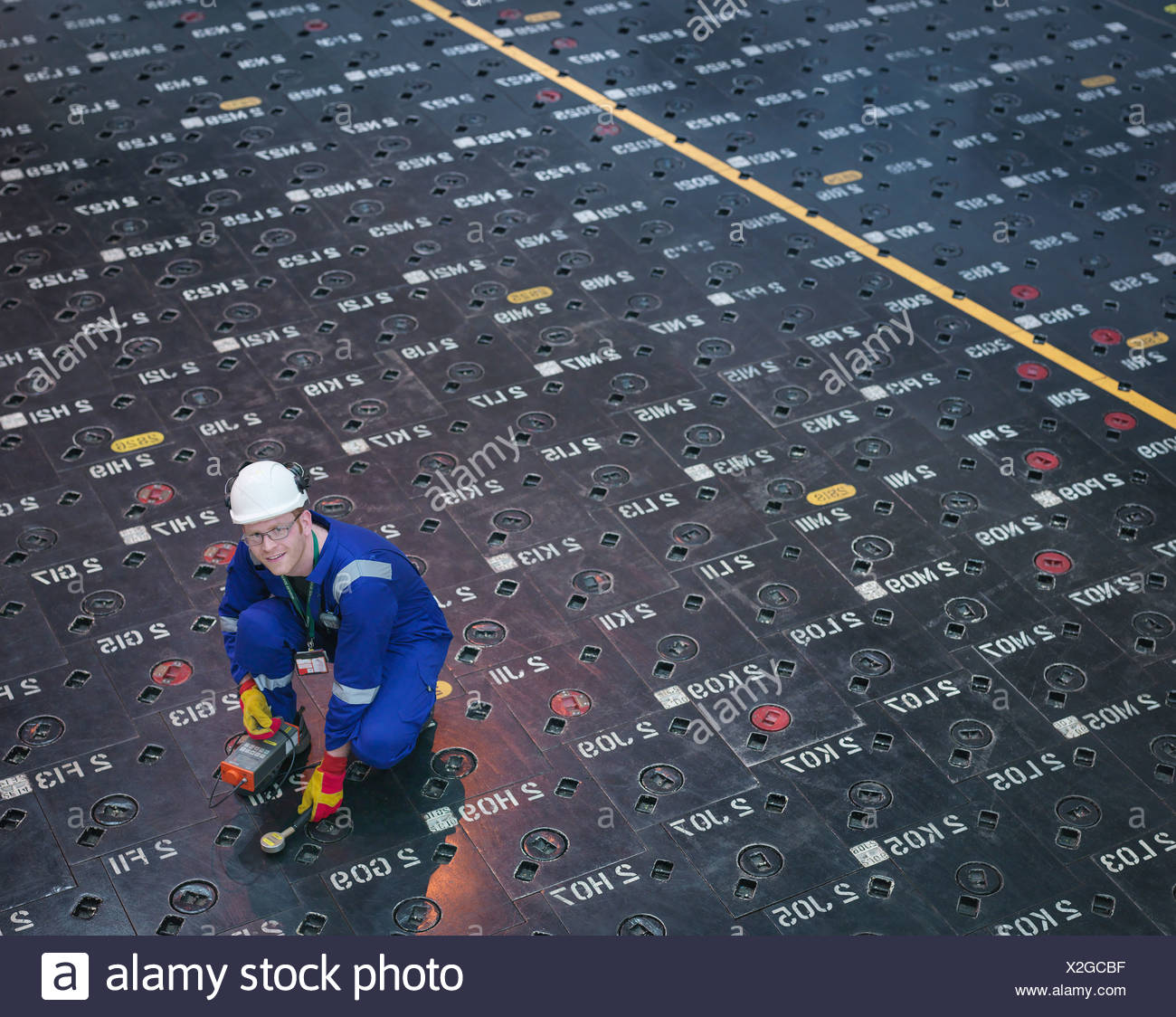Engineer using sensors on pile cap in nuclear power station, portrait - Stock Image