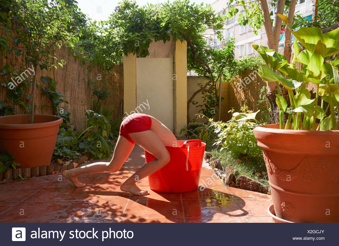 Girl in bikini bottoms bending headfirst into red bucket on patio - Stock Image
