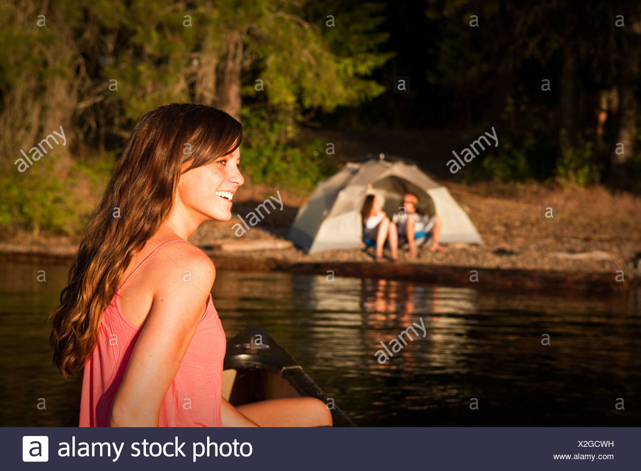 A happy young woman smiles while canoeing on a camping trip on a lake in Idaho. - Stock Image