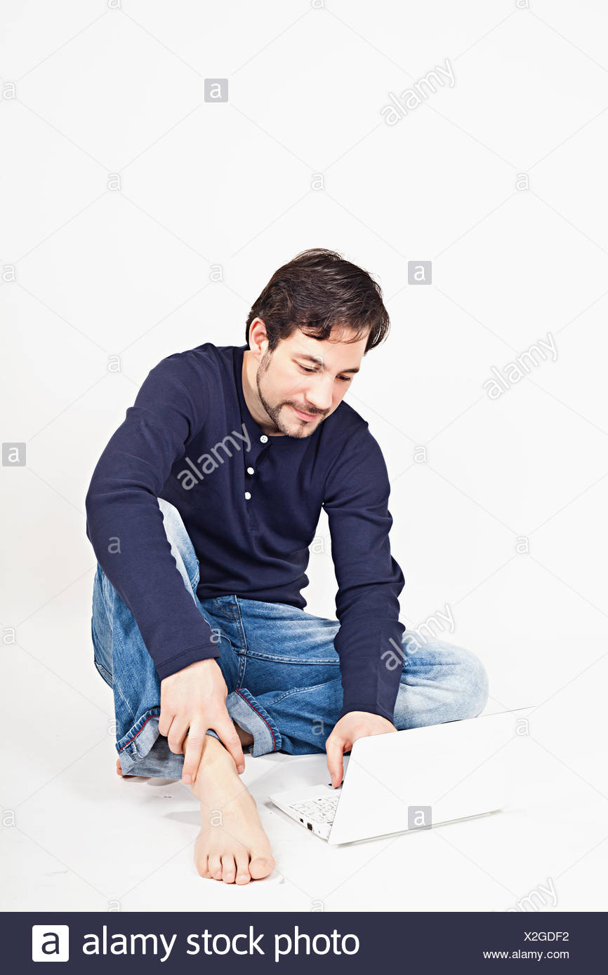 young man working on laptop while sitting on the floor - Stock Image