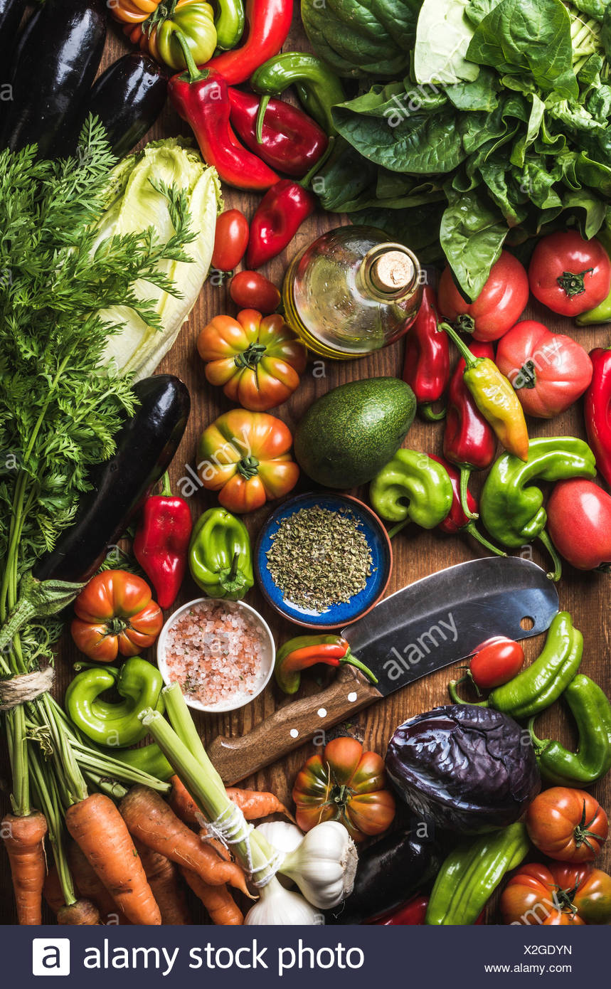 Variety of fresh raw vegetables for healthy cooking or salad making and carving knife, top view. Diet or vegetarian food concept - Stock Image