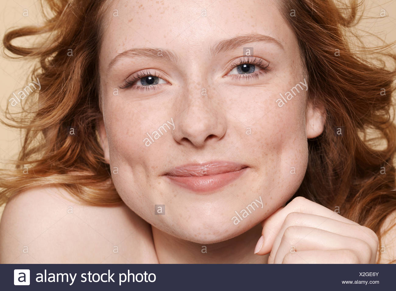 Studio shot of young woman with curly red hair, hand on chin - Stock Image