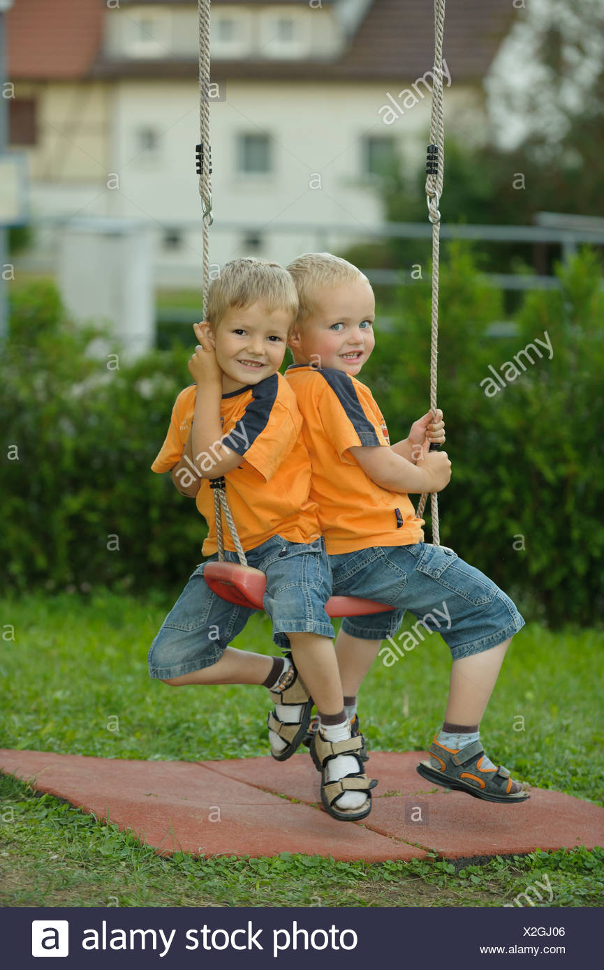 Two little boys, 3 and 4 years, on a swing - Stock Image