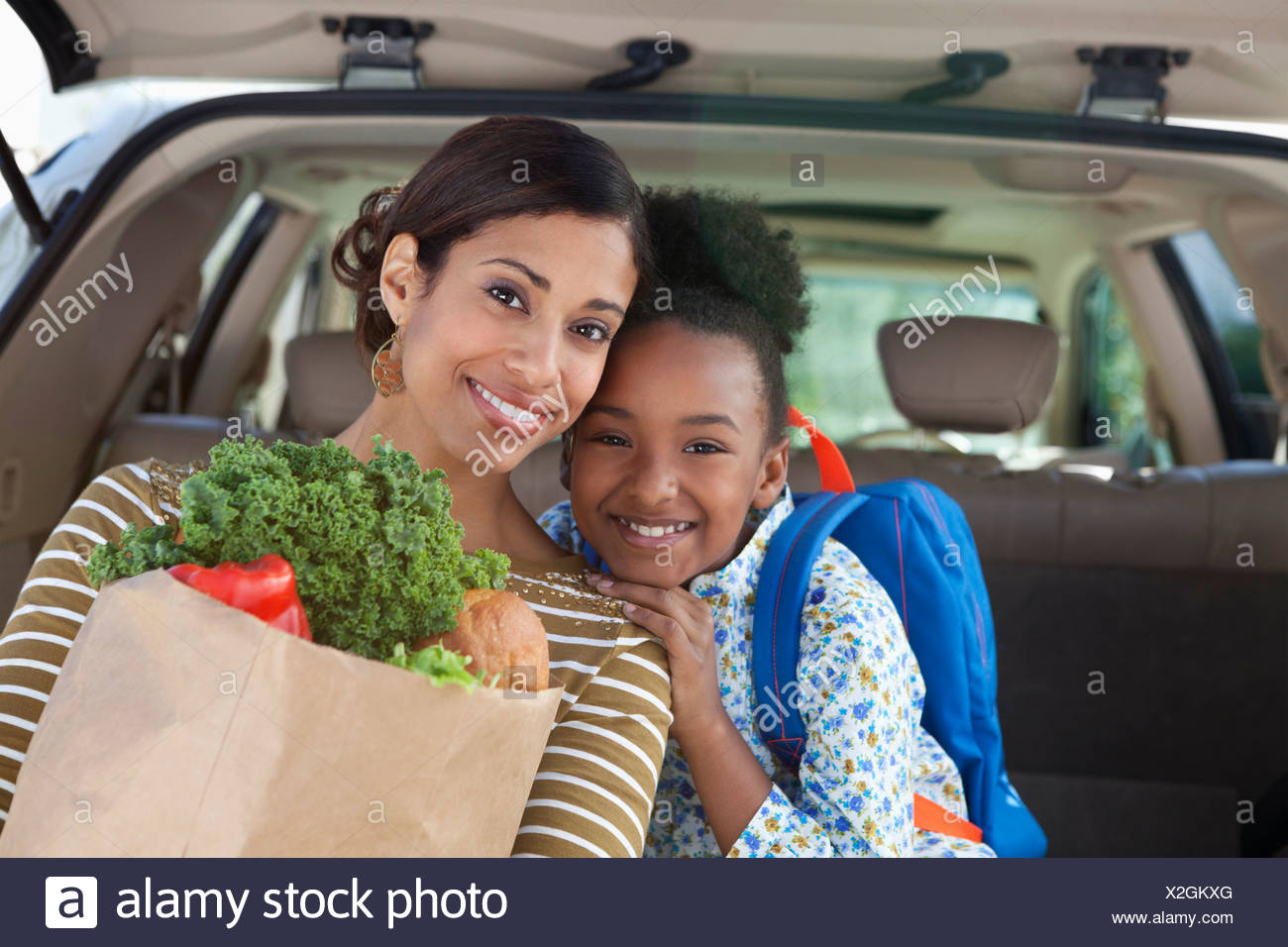 Mother and daughter unloading groceries from car - Stock Image
