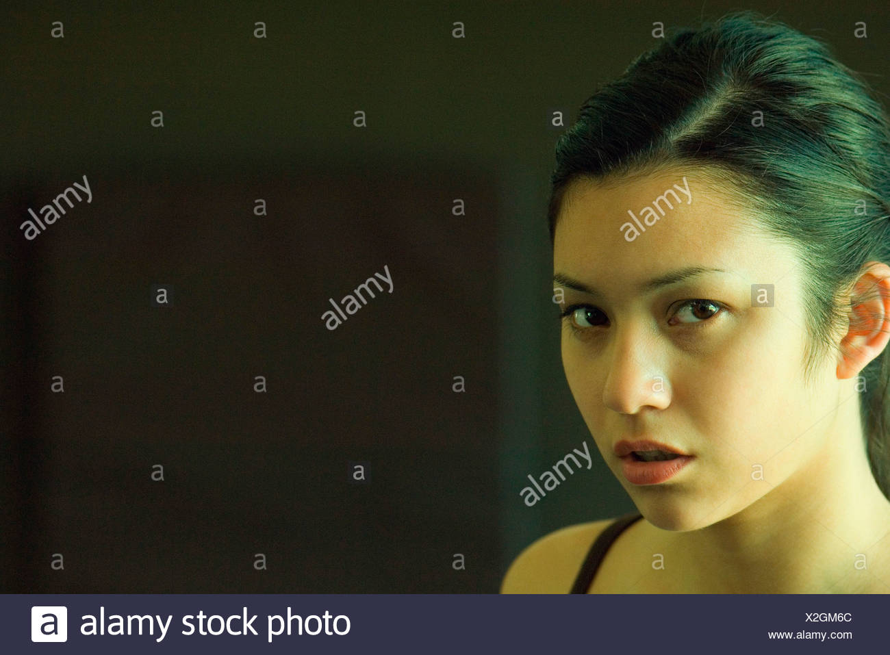 Young woman scowling at camera, portrait - Stock Image