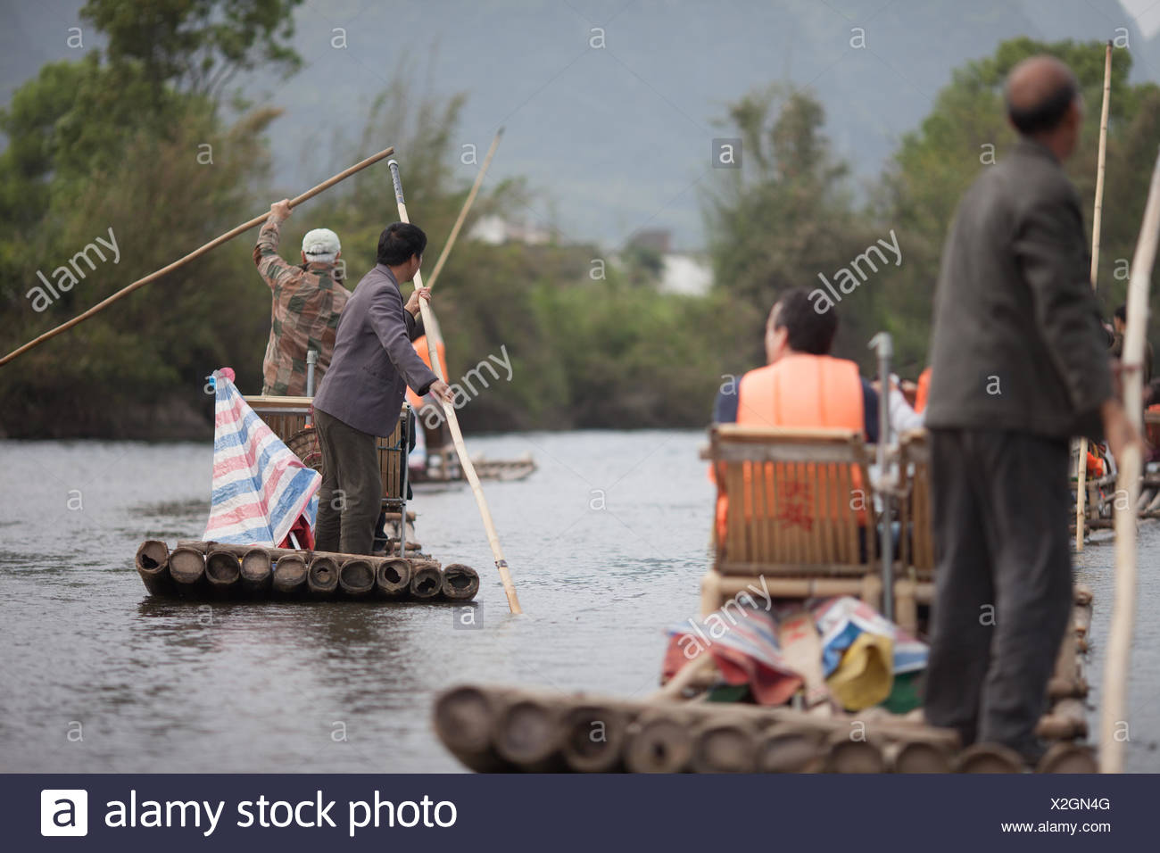 Boatmen Punting Wooden Rafts Along River - Stock Image