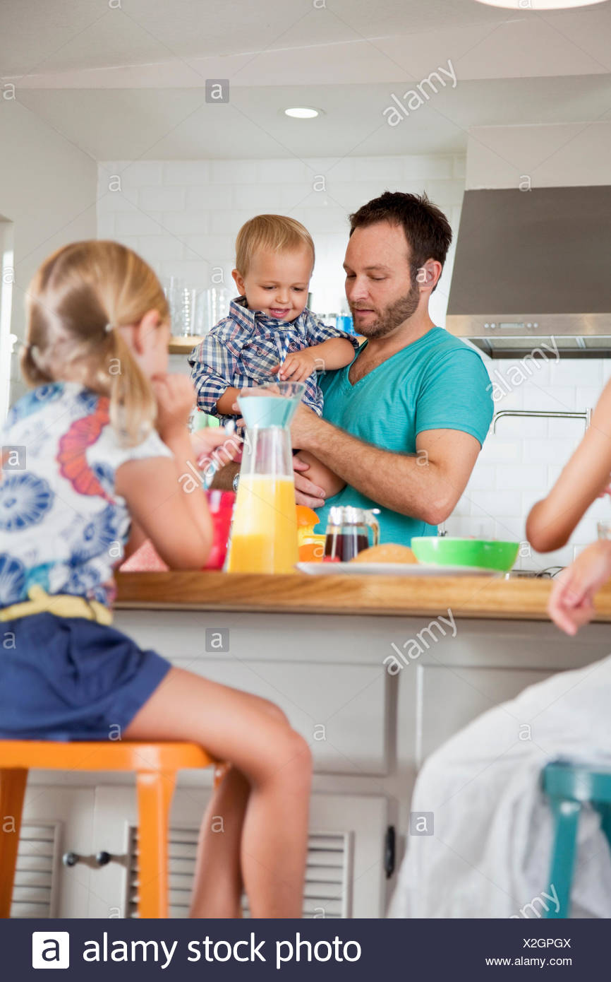 Father multi tasking breakfast with son and daughters - Stock Image