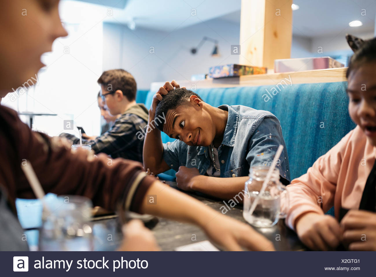 Tween boy playing game with friend at cafe table - Stock Image
