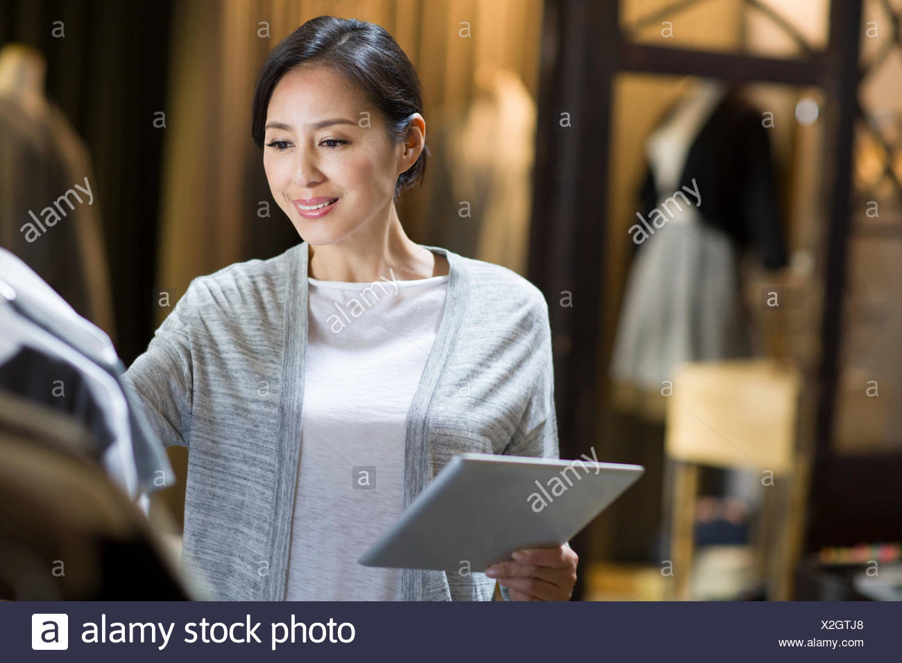 Clothing store owner with digital tablet - Stock Image